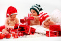 Three babies in xmas costumes playing with gifts Royalty Free Stock Photography
