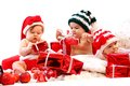 Three babies in xmas costumes playing with gifts over white background Royalty Free Stock Image