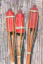 Three bamboo fire torch on cane fence Stock Photo