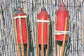 Three bamboo fire torch on cane fence Royalty Free Stock Photography