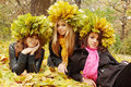 Three beauties in a wreath young womans wearing of autumn leaves Stock Photos
