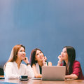 Three beautiful Asian girls looking upward to copy space while working at cafe Royalty Free Stock Photo