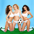 Three beautiful athletic women in lingerie sporty posing on their knees holding a soccer ball with alluring inviting looks on a Stock Photography