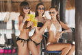 Three beautiful girls in a bar on the beach Royalty Free Stock Photo