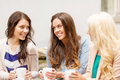 Three beautiful girls drinking coffee in cafe holidays food and tourism concept Royalty Free Stock Images