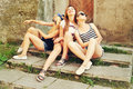 Three beautiful girls rest on the street. Beautiful happy girls in sunglasses on the urban background. Young active people. Outdoo Royalty Free Stock Photo
