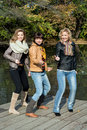 Three beautiful joyful woman posing on a pier at the lake women standing and Stock Photography