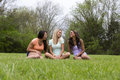 Three beautiful laughing woman sitting in the park women of different races sit and laugh with eachother Royalty Free Stock Photos