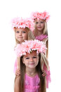 Three beautiful little girls with pink wreaths Stock Photo