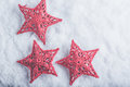 Three Beautiful magical vintage red stars on a white snow background. Winter and Christmas concept Royalty Free Stock Photo