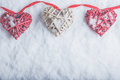 Three beautiful romantic vintage hearts are hanging on a red band on a white snow background. Love and St. Valentines Day concept. Royalty Free Stock Photo