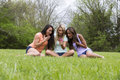 Three beautiful surprised woman sitting in the park women of different races sit and are at what they see on a phone Stock Photography