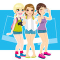 Three beautiful tourist girls happy taking photos enjoying their vacation destination Royalty Free Stock Image
