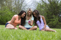 Three beautiful woman looking at phone women of different races sit in the park and watch a video on a Royalty Free Stock Photos