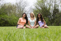 Three beautiful woman sitting in the park women of different races sit and smile Stock Photos