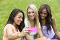 Three beautiful woman take a photo women of different races sit in the park and group Royalty Free Stock Image