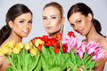 Three beautiful women with fresh spring tulips Royalty Free Stock Photo
