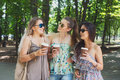 Three beautiful young boho chic stylish girls walking in park. Royalty Free Stock Photo