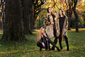 Three beautiful young models in autumn elegant clothes posing at central park new york location for fall fashion photo shoot Stock Photography