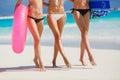 Three beautiful young women on the beach in a bikini.