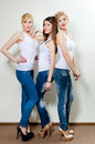 Three beautiful young women in blue jeans looking up girls and high heels studio shot on white Stock Photos