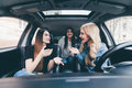 Three beautiful young women friends have fun together in the o car as they go on a road trip together for their summer vacation Royalty Free Stock Photo