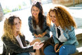 Three beautiful young women using they mobile phone in the street. Royalty Free Stock Photo