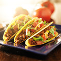 Three beef tacos with cheese lettuce and tomatoes shot in square format selective focus has lens flare coming from Stock Photo