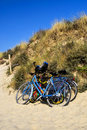 Three bicycles parked against sand dunes Royalty Free Stock Image