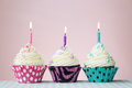 Three birthday cupcakes against pink Royalty Free Stock Images
