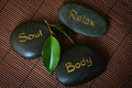 Three black massage stone with words body soul and relax Stock Photography