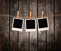 Three blank instant photos on the clothesline Royalty Free Stock Photo