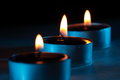 Three blue candles are glowing in the darkness Royalty Free Stock Photo