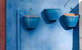 Three blue flowerpots ornamental on wall closeup Royalty Free Stock Images