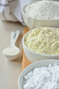 Three bowls with gluten free flour rice millet and potato starch and spoon xanthan gum Stock Photography