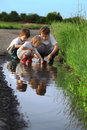 Three boy play in puddle outdoors Royalty Free Stock Photo