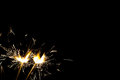 Three bright festive Christmas sparklers on black with free space Royalty Free Stock Photo