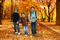 Three brothers in autumn park happy laughing black boys happy years old going together holding hands the wearing backpacks and Royalty Free Stock Photography