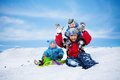 Three brothers having fun on winter day sitting the snow and playing together Royalty Free Stock Photos