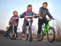 Three brothers ride bikes outdoors Stock Images