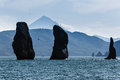 Three brothers rocks in avacha bay on background vilyuchinsky volcano kamchatka beautiful seascape view natural monument of Stock Image