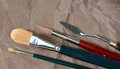 Three brushes and palette knife lie on brown paper Royalty Free Stock Photo