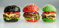 Three burgers with beef patties and salad trimming Royalty Free Stock Photo