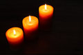 Three burning candles on a dark background closeup of wooden table Royalty Free Stock Photography