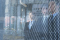 Three business people behind a glass wall looking out unrecognizable faces Stock Image