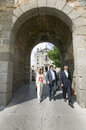 Three business people walk through gate of walled city, Avila Spain, an old Castilian Spanish village Royalty Free Stock Photo