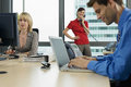 Three business people working in office, man using laptop, woman using PC, second woman using phone Royalty Free Stock Photo