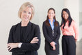 Three business women standing together of varying ethnicities in suits smiling and looking at camera in office Stock Photo