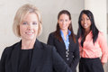 Three business women standing together of varying ethnicities in suits smiling and looking at camera in office Stock Photography