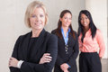Three business women standing together of varying ethnicities in suits smiling and looking at camera in office Stock Photos